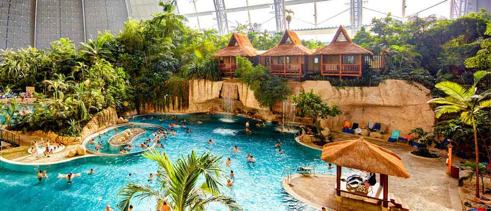 tropical island waterpark people swimming blue water green tropical trees bamboo huts