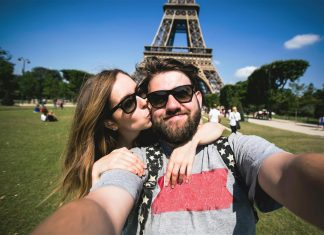 man and woman take selfie at eiffel tower