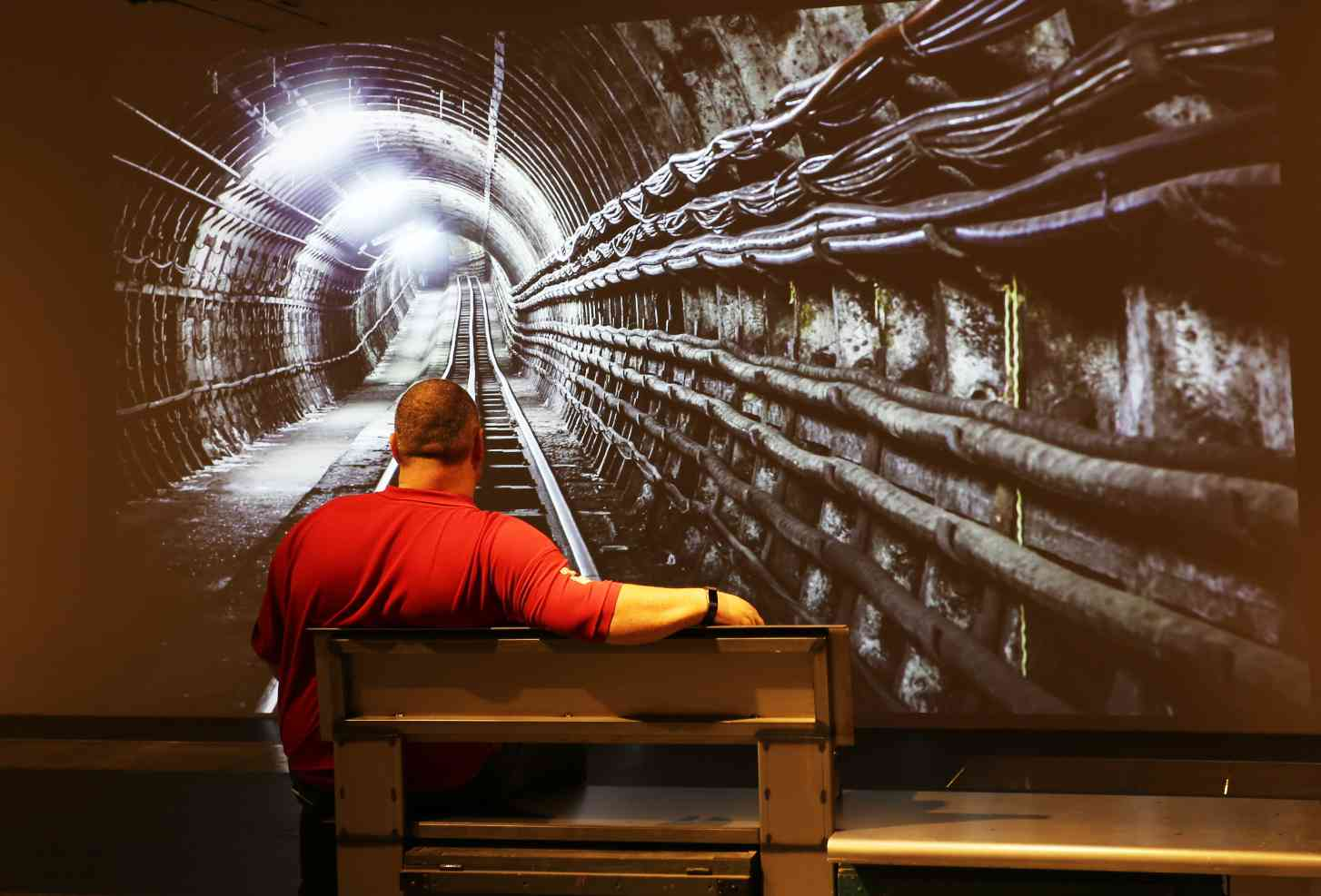 man watching digital projection mail rail tunnel