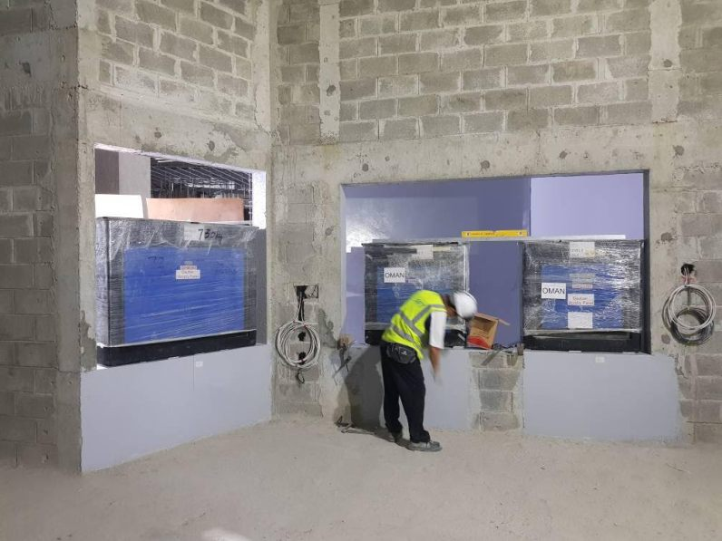 workman in hardhat installing tanks at oman aquarium
