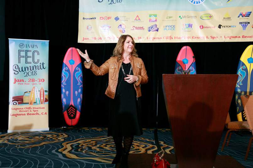 woman giving talk at iaapa fec summit with surfboards in background