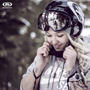 girl putting on ski helmet and goggles extreme