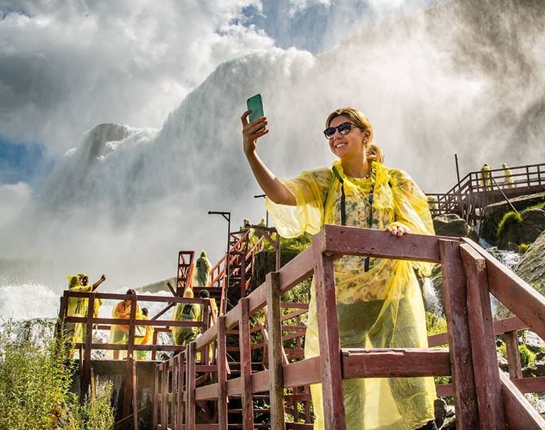 woman in poncho takes selfie at niagara falls cave of the winds