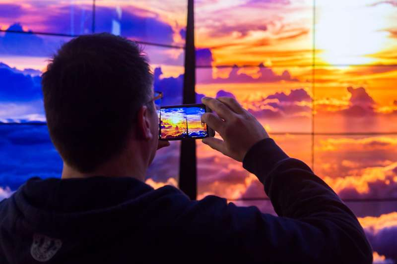 man takes image on smartphone of LED panels showing sunset