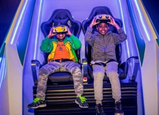 two boys wearing headsets sit in immotion vr pod at legoland discovery center boston usa
