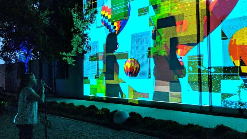 woman interacts with participation projection mapping by aoa