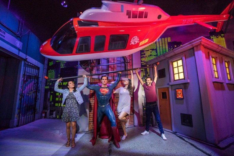 guests hold up helicopter with superman at justice league attraction madame tussauds orlando