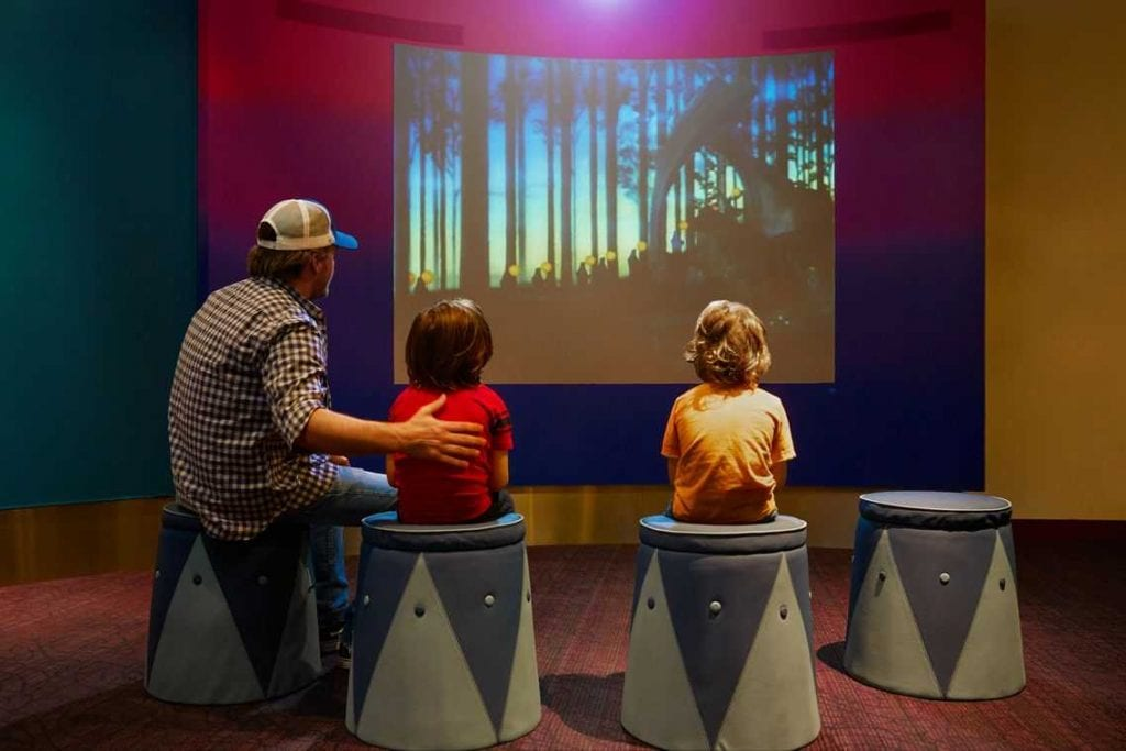 Three visitors watching an animated video at the Walt Disney Family Museum