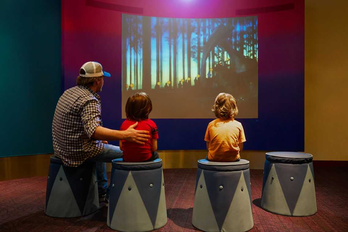 Three visitors watching an animated video