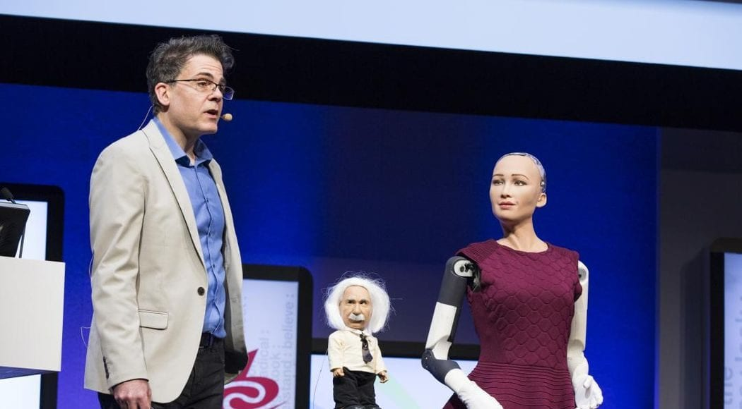 Speaker at IBC with mini figure of Einstein and female robot