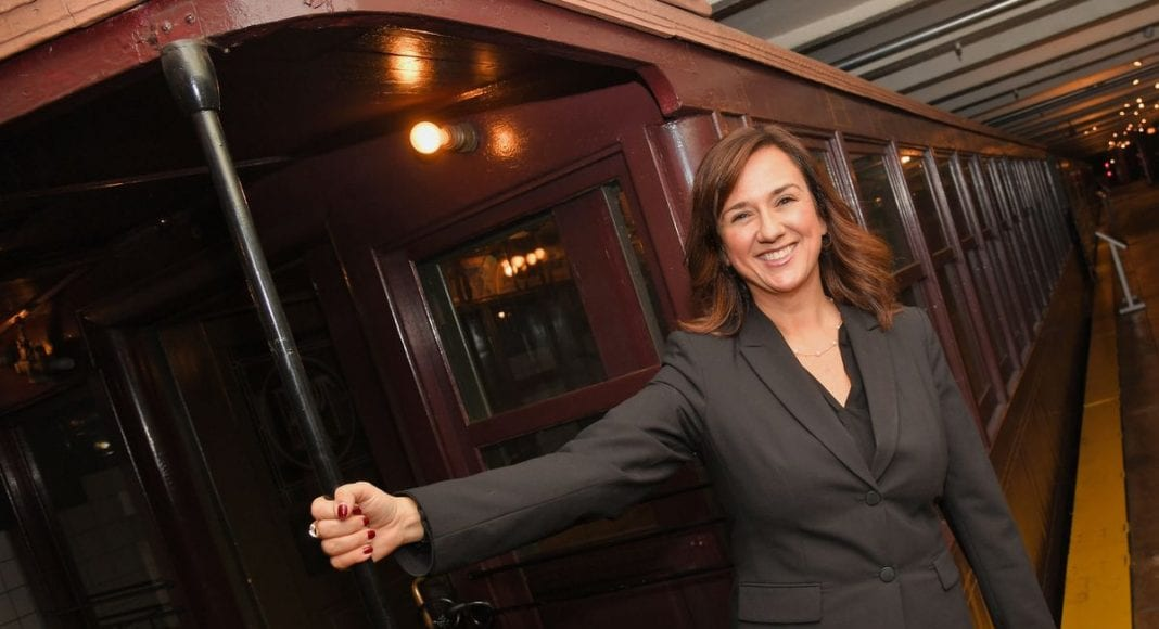 Smiling Concetta Bencivenga hanging from the end of a stationary train
