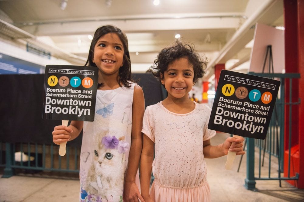 Two smiling children each holding a signage to Downtown Brooklyn