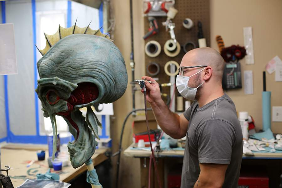 man sprays paint on alien head at animax designs