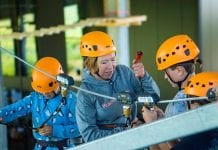 woman securs saferoller belay system at aspen-antwerpen indoor ski resort