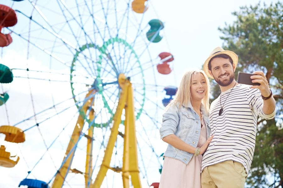 Couple taking a selfie in front of a ferris wheel, The Experience Engine