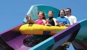 4 Passengers on a raft going down a purple and blue water coaster
