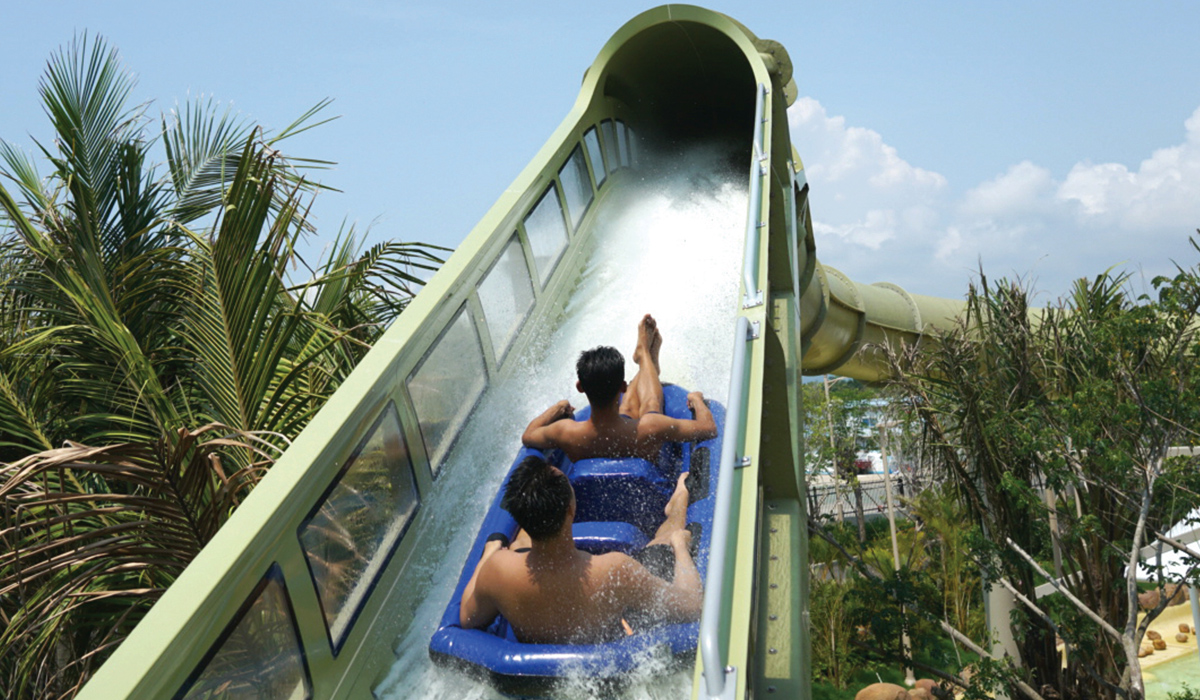 Two men in a raft going up a water coaster