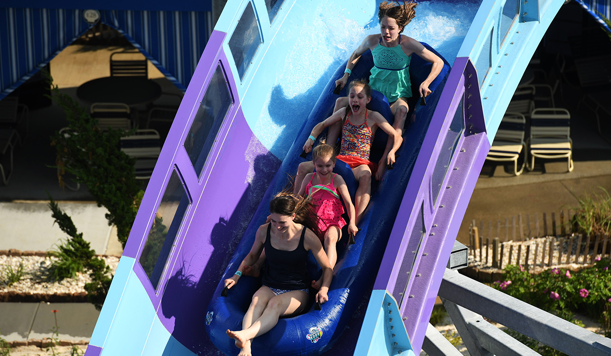 Four women in a four person raft flying down a Hydro Magnetic Rocket water coaster