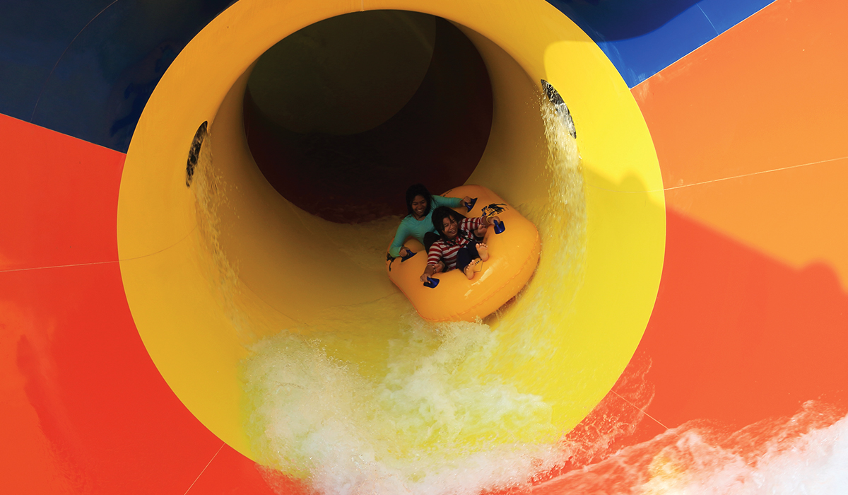 Inside view of two individuals on a yellow raft as tehy are about to exit a pipeline
