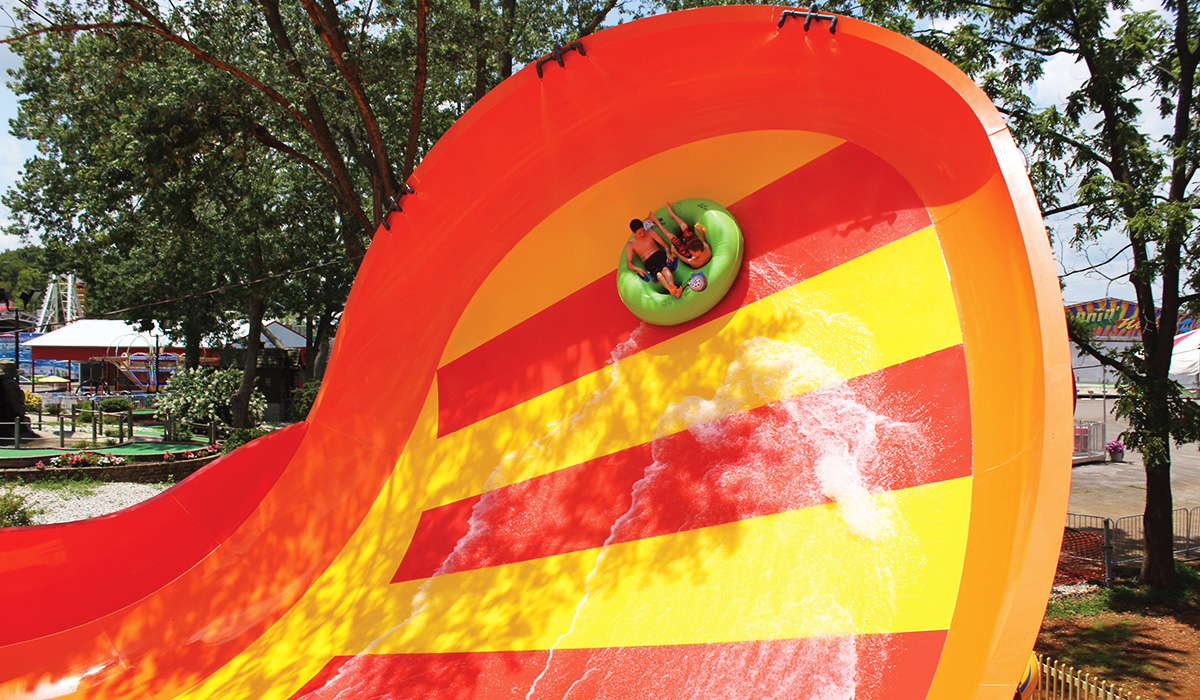 Two person raft at the peak of a orange and yellow water slide wall