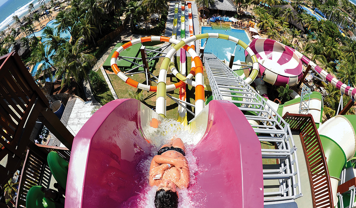 Landscape, top view of an individual about to go down a very steep pink Freefall water slide.