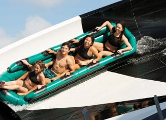 Close-up image of four teenagers riding on a raft riding the side of a flying saucer