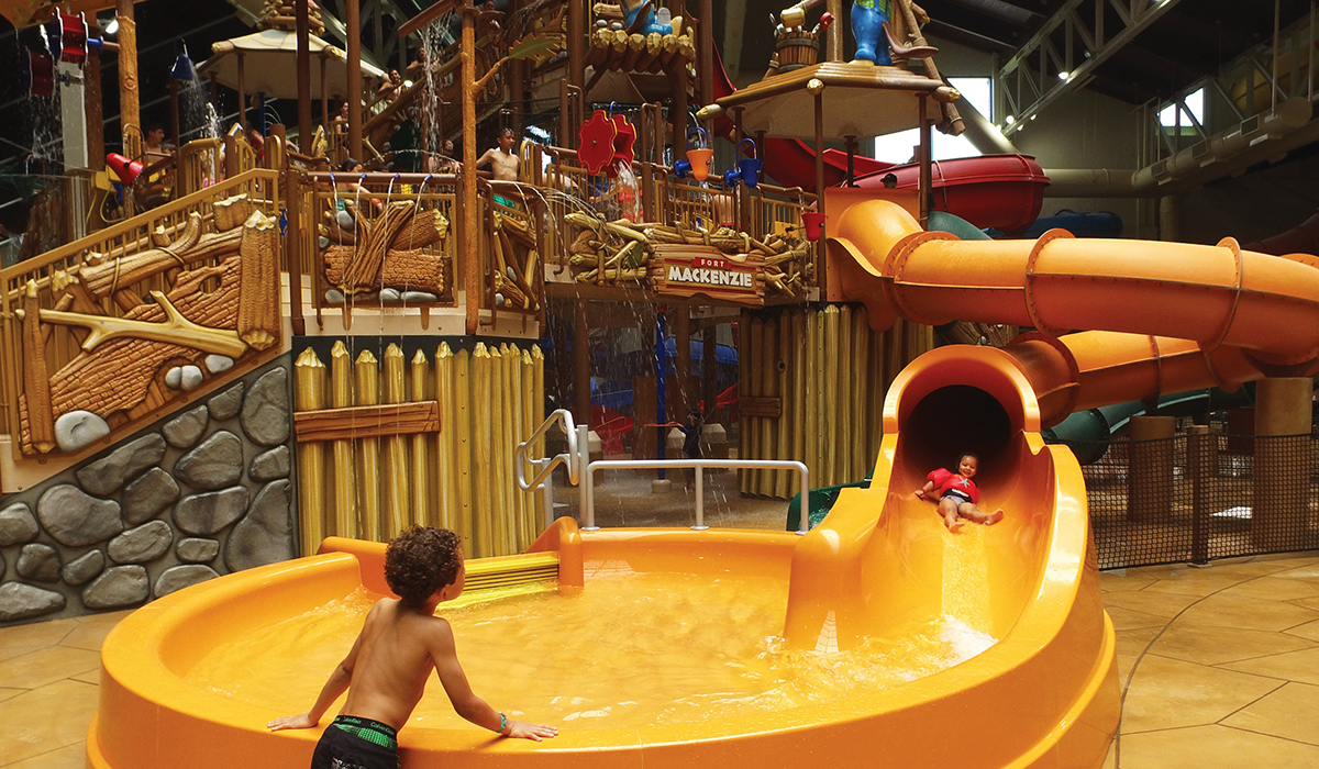 Medium shot of a child about to slide down a kids slide while another child watches