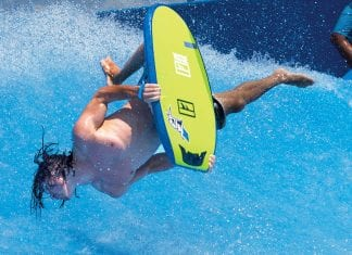 Man diving head first into a wave with a surfboard