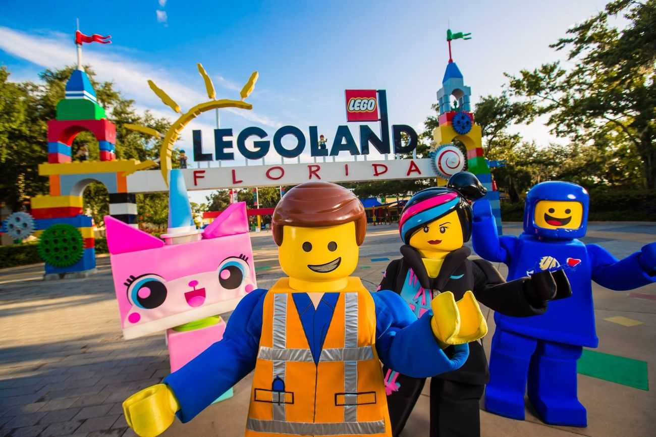 Unikitty, Emmet, Wyldstyle and Benny from THE LEGO MOVIE WORLD posing in front of Legoland Florida entrance