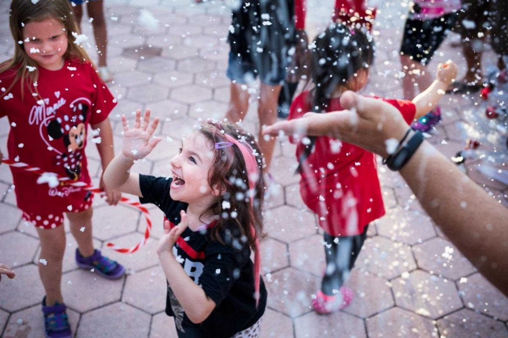 Happy children enjoying snowfall at Give Kids The World