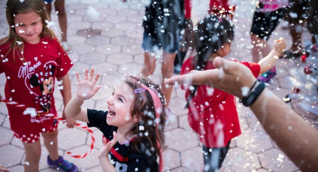 Happy children enjoying snowfall at Give Kids The World