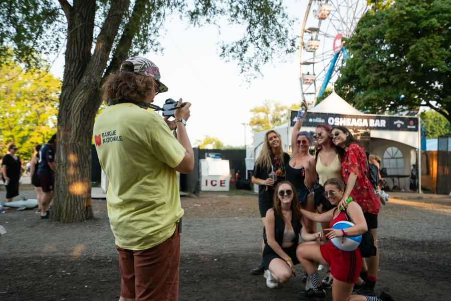 Osheaga Music and Arts Festival staff taking picture for a group of guests outside the Osheaga Bar