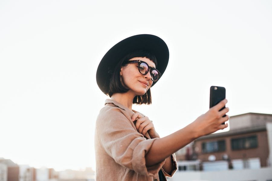 Girl with hat and glasses taking a selfie