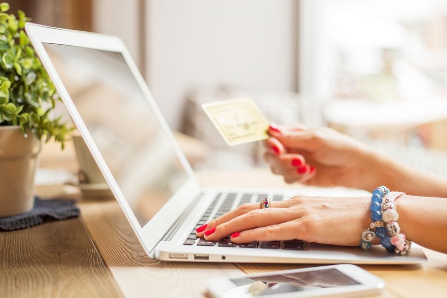 Woman holding a credit card and using her laptop