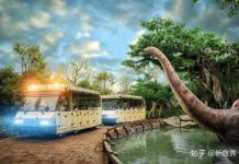 Super 78 ride Dino Tour trams going past animatronic dinosaur in rainforest